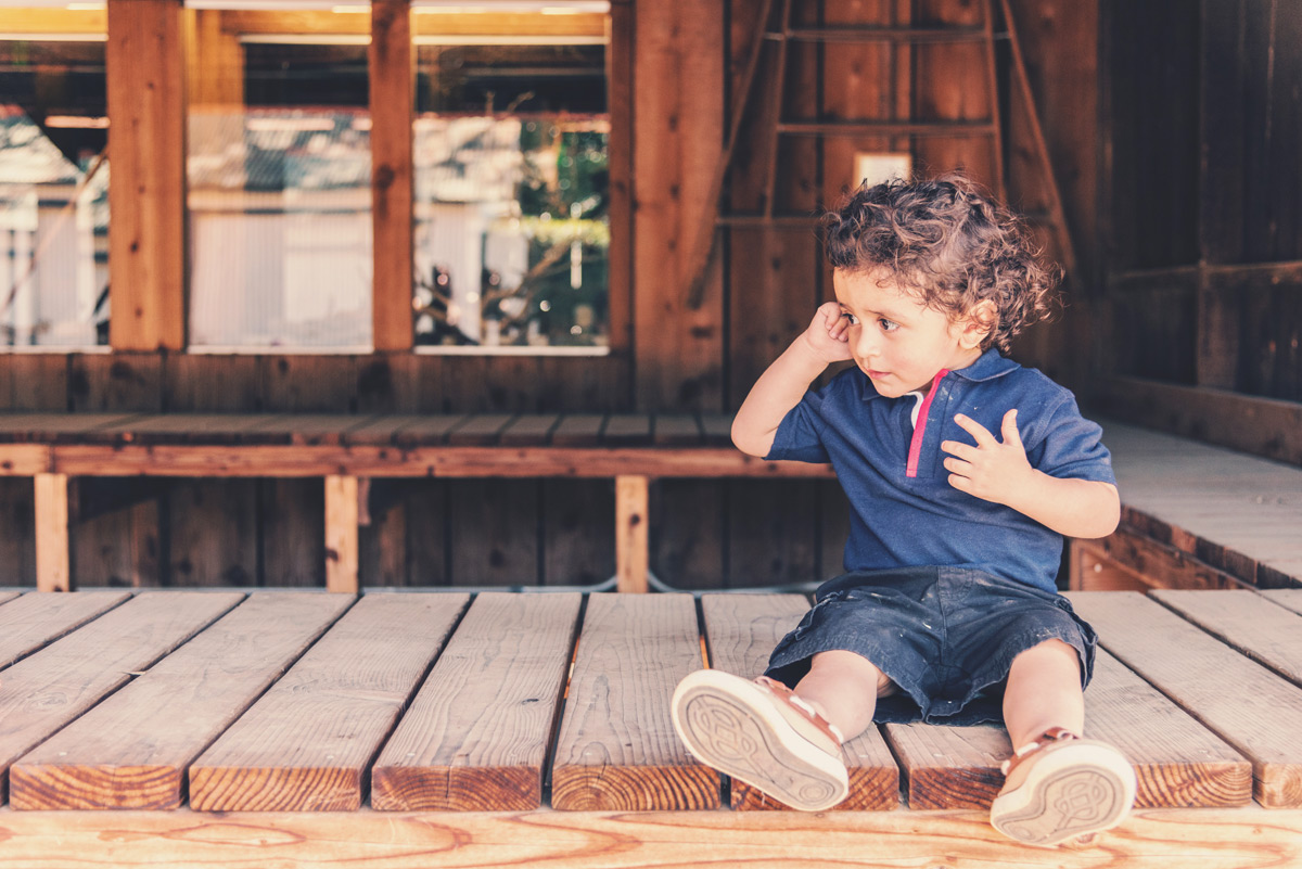 Toddler sitting on porch during summer
